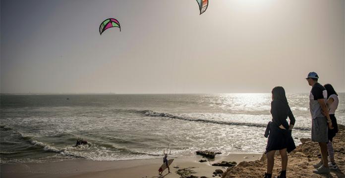 Des touristes regardent des kitesurfeurs sur une plage de Dakhla en octobre 2019 au Maroc. AFP